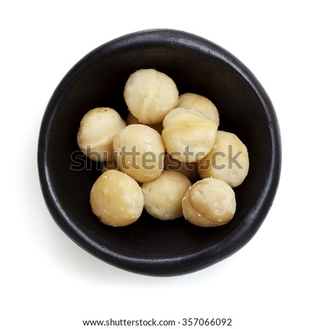 Macadamia nuts in black bowl.  Overhead view.  Isolated on white. - stock photo