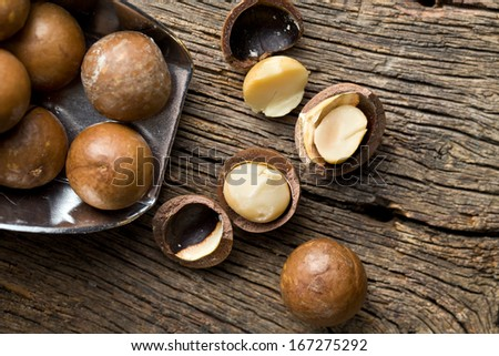 macadamia nuts on scoop on wooden table - stock photo