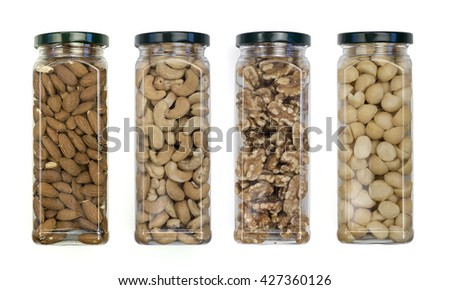 Macadamia nuts, walnuts, cashews, almonds packed in plastic jars on the background - stock photo