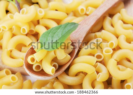 macaroni and basil in wooden spoon - stock photo