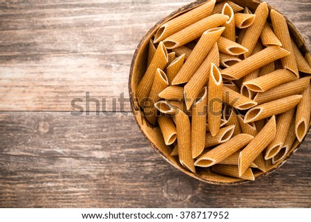 Macaroni on the bowl, wooden background. - stock photo