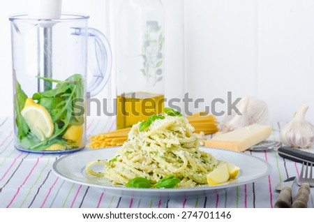 Macaroni with pesto, pesto with olive oil, herbs, nuts and Parmesan, sprinkled with fresh basil and parmesan - stock photo