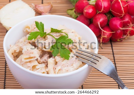 Macaroni with tuna, mayonnaise, onion, garlic and sesame - stock photo