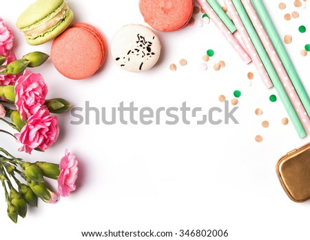 Macarons, paper straws in pastel color, pink flowers and confetti on the white background, top view - stock photo