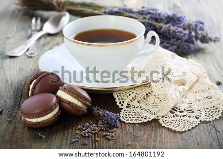 Macarons with lavender cream and a cup of tea. - stock photo