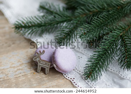 Macaroons and christmas spices on wooden ground