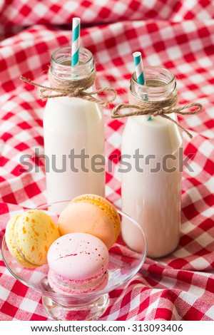 macaroons and milk in a bottle with striped straws