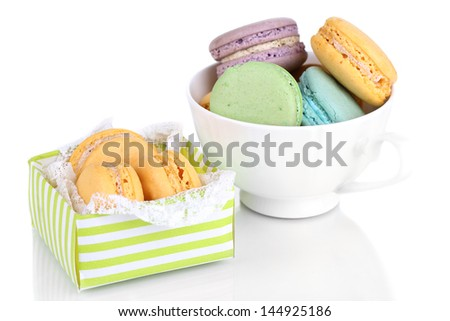 Macaroons in cup and box isolated on white
