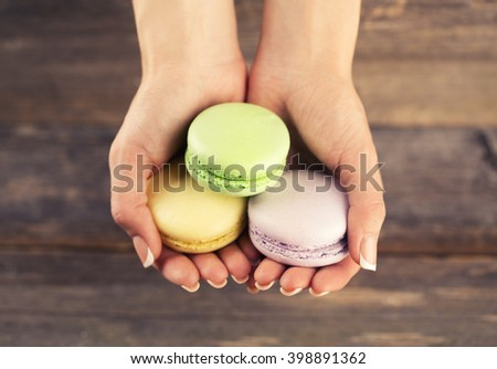 Macaroons in wooman hands on Wood background