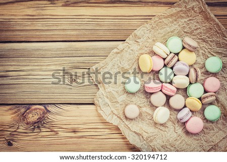 Macaroons on  crumpled parchment against the backdrop of wooden boards - stock photo