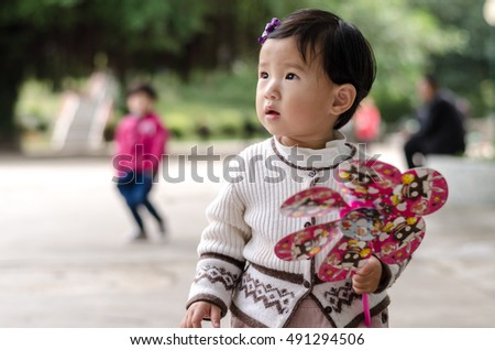MACAU, CHINA - APRIL 6, 2013_Unidentified cute little chinese girl holding a colorful pinwheel in hand in Macau, China.