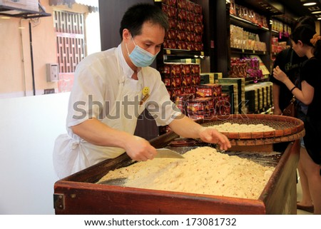 MACAU, CHINA - JULY 9, 2012 : Visitors buys Chines food at Macau Historic Center on July 9, 2012 in Macau, China.The Historic Center of Macao was inscribed on the UNESCO World Heritage List in 2005. - stock photo