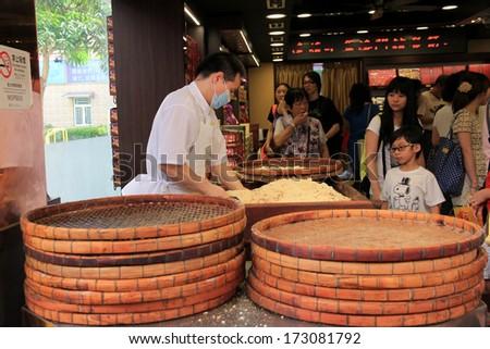 MACAU, CHINA - JULY 9, 2012 : Visitors buys Chinese food at Macau Historic Center on July 9, 2012 in Macau, China.The Historic Center of Macao was inscribed on the UNESCO World Heritage List in 2005. - stock photo