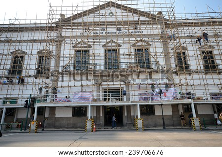 MACAU, CHINA - NOV 19: Workers repair Civic And Municipal Affairs Bureaumore in Macau on November 19, 2014. The Historic Center of Macau was inscribed on the UNESCO World Heritage List in 2005. - stock photo