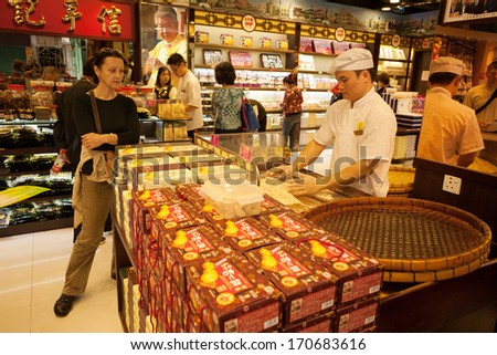 MACAU, CHINA - OCTOBER 31: Confectioner manufactures biscuits in candy store. Manufacture and sale of confectionery products is very popular business in Macau.