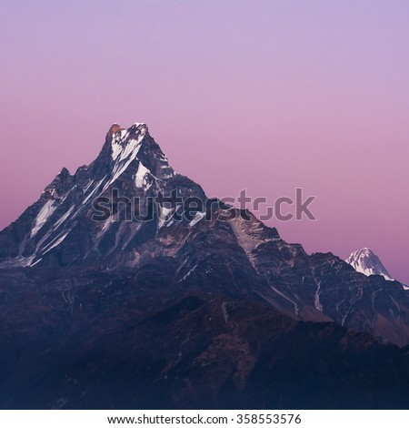 Machapuchare or Fishtail peak with sunset sky. it is a mountain in the Annapurna Himal of north central Nepal. - stock photo