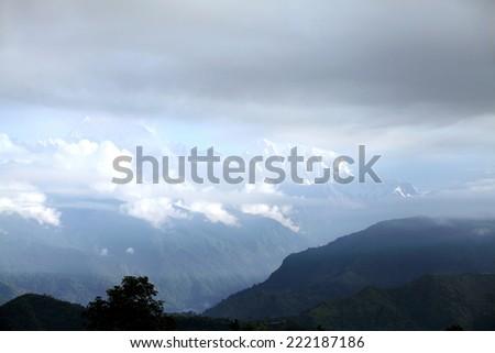 Machhapuchhre and Annapurna range through the clouds - stock photo
