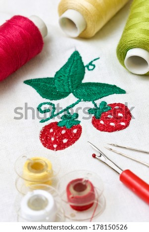 machine embroidery image strawberry, tools for embroidery: thread, needle, bobbin - stock photo
