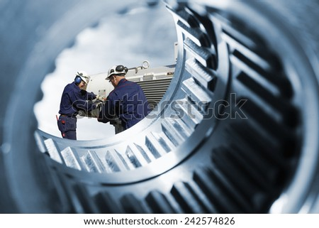 machine engineers seen through a giant gear and cogwheel axle - stock photo