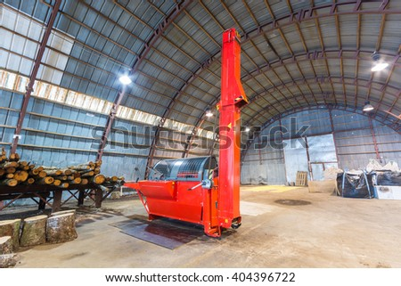 Machine for chopping firewood. Firewood processor in big warehouse. - stock photo