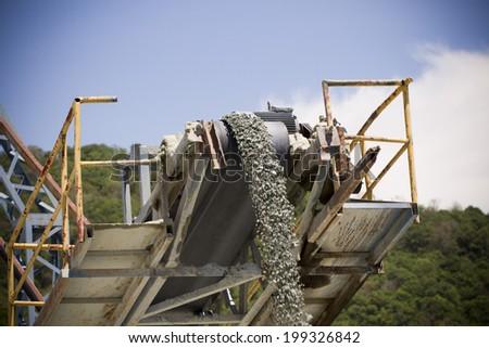 Machine pouring stones - stock photo
