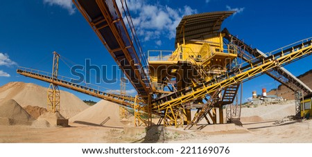 Machinery and classification according gravel size distribution via conveyor belts and piles of sand and records in mountain landscape  - stock photo