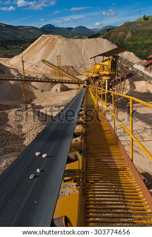 Machinery and classification according gravel size distribution via conveyor belts  in mountainous landscape with piles of gravel and sand  - stock photo