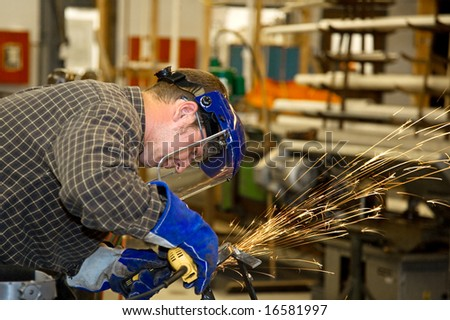 Machinist grinding metal in a factory.  Horizontal with room for text.  Authentic and accurate content depiction in compliance with industry code and safety standards. - stock photo