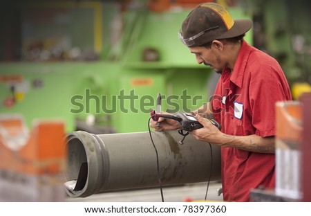 machinist in a factory checking quality of work - stock photo