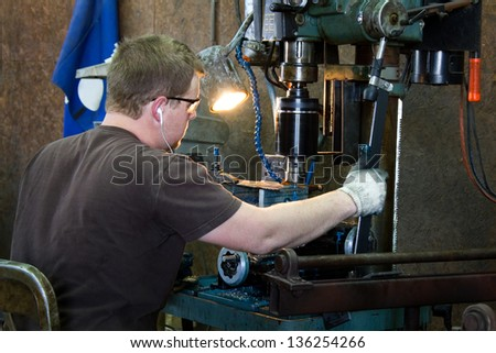 Machinist taps threads into steel using a drill press in production work in a metal shop. - stock photo