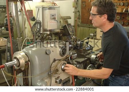 Machinist working a metal lathe - stock photo