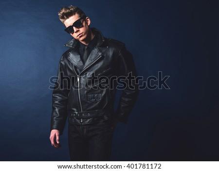 Macho retro 1950s fashion man wearing sunglasses and leather jacket. - stock photo