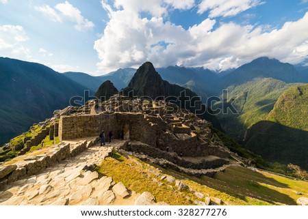 Machu Picchu partially illuminated by the last sunlight. Wide angle view from the terraces with scenic sky and glowing footpath in the foreground.