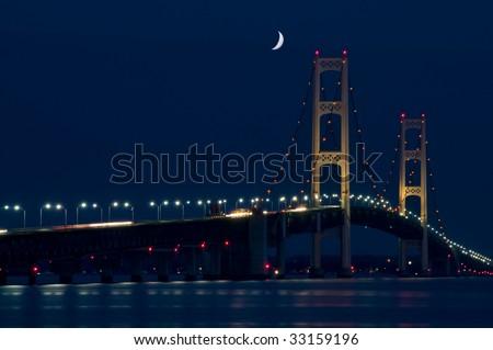 Mackinac Bridge spanning the Upper and Lower Peninsula of Michigan. Nigh shot with dark blue sky with crescent moon. - stock photo
