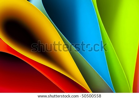Macro and abstract image of colored card stock (blue,red,pink,yellow and green) with a tear drop or elliptical shape on a black background. Excellent image for business background. - stock photo