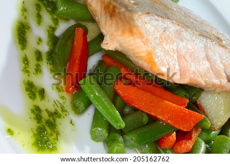 macro appetizing piece of fish on a bed of vegetables and green beans on a white plate in a restaurant