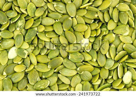 Macro background texture of green pumpkin seeds - stock photo