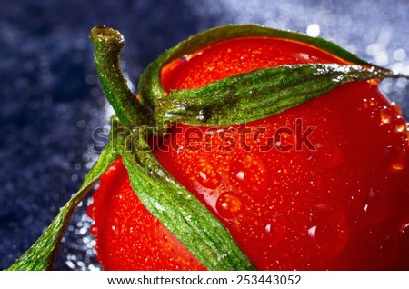 Macro close up of a cherry tomato with water drops and bokeh background - stock photo