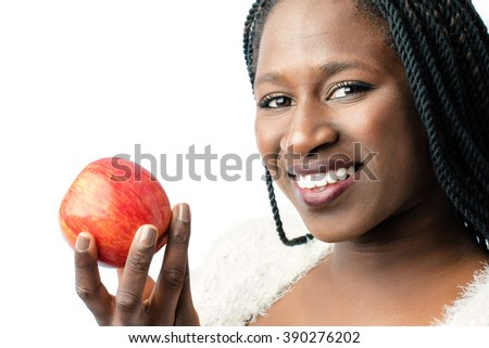 Macro close up of attractive african girl with toothy smile holding red apple. Isolated on white background. - stock photo