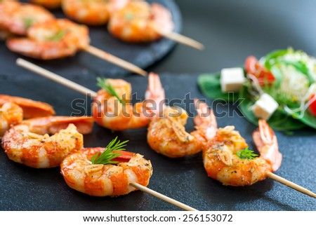 Macro close up of catering shrimp brochettes grilled with herbs. Out of focus salad in background. - stock photo