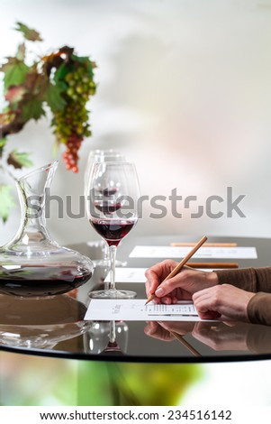 Macro close up of female hand writing notes on paper at wine tasting. - stock photo
