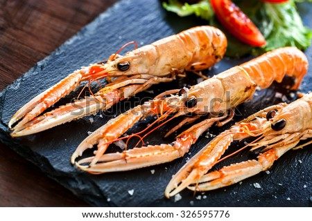 Macro close up of fresh grilled craw fish platter with green salad served on elegant black tile. - stock photo