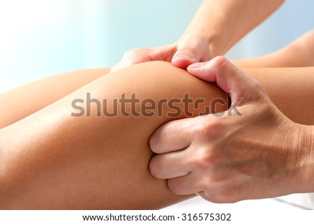 Macro close up of hands doing manipulative healing massage on female calf muscle. - stock photo