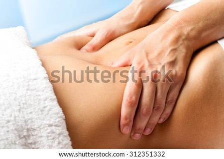 Macro close up of hands massaging female abdomen.Therapist applying pressure on belly. - stock photo