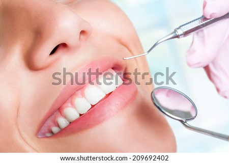 Macro close up of Human teeth with hatchet and mouth mirror - stock photo