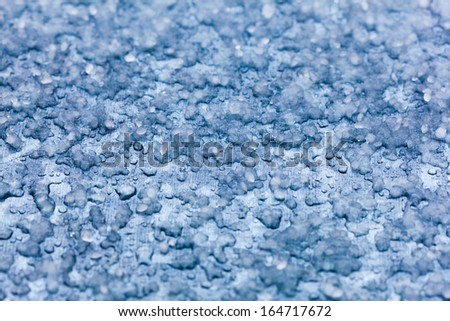 Macro close-up of melt snow as blue background or texture. Winter and seasonal weather.