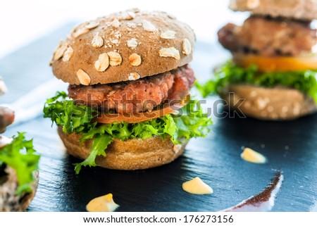 Macro close up of mini organic hamburger in catering buffet. - stock photo