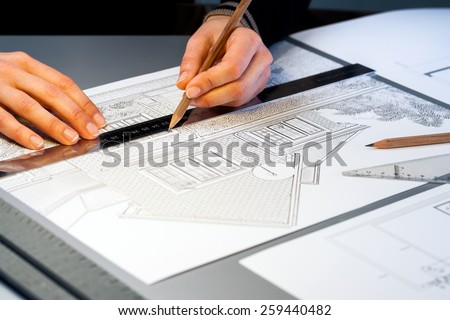Macro close up of quantity surveyor working on architectural layout. - stock photo