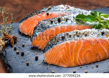 Macro close up of smoked salmon portions seasoned with aromatic herbs. - stock photo