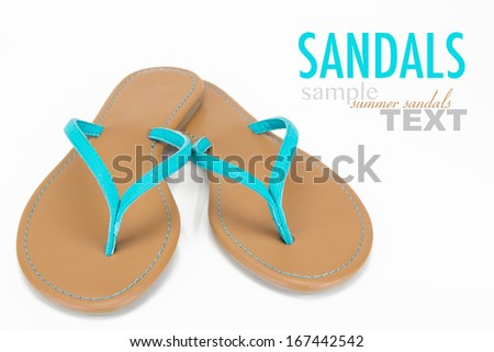 Macro close up of stylish aqua blue beach sandals or flip flops with sample text. Shot in studio on a white background. - stock photo
